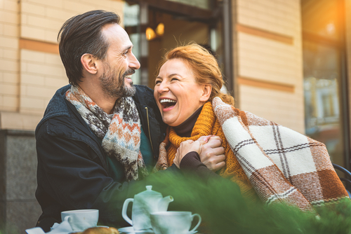 middle-aged man and woman smiling at a cafe outdoors